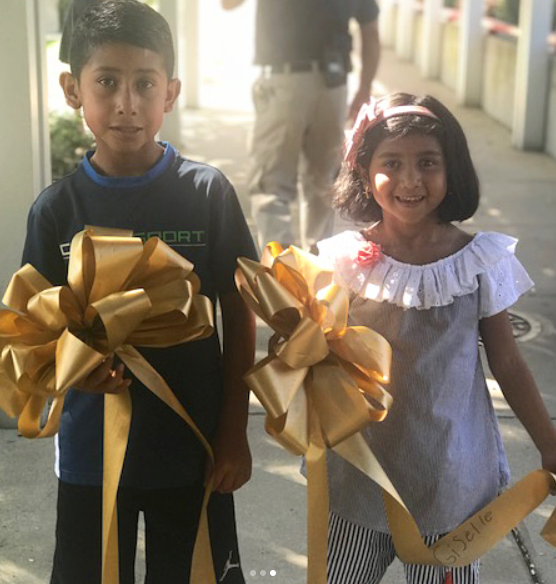 Gigi and brother with ribbons at ribbon ceremony
