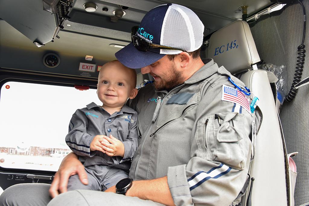 Pilot holding baby in flight suit