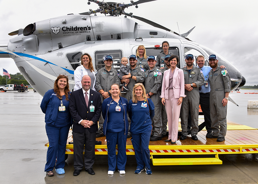 Group of people posing for photo beside helicopter