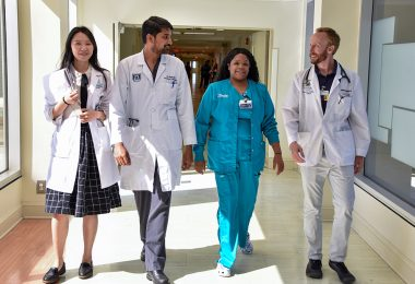 Four medical employees walking in hallway